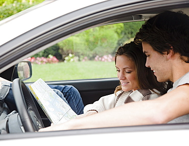 Couple in car looking at map