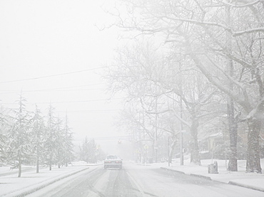 USA, New York State, Rockaway Beach, car on road during blizzard
