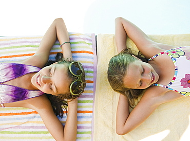 USA, New York, Two girls (10-11, 10-11) lying on towels