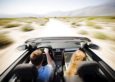 Couple driving through desert in convertible car