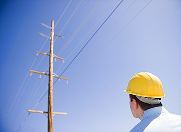 Man in hard hat looking at telephone pole
