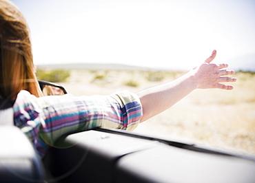 USA, California, Palm Springs, Coachella Valley, San Gorgonio Pass, Woman stretching arm outside convertible car