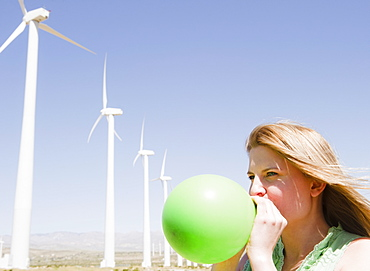 USA, California, Palm Springs, Coachella Valley, San Gorgonio Pass, Woman blowing green balloon with wind turbines in background