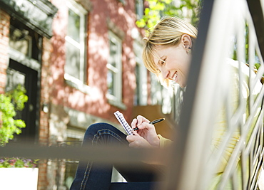 USA, New York, Williamsburg, Brooklyn, Smiling woman writing diary