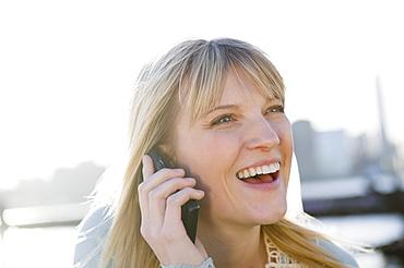 USA, Brooklyn, Williamsburg, Portrait of blonde woman talking on mobile phone