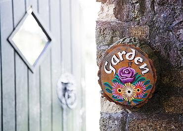 Ireland, County Westmeath, Garden sign on stone wall