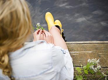 Roaring Brook Lake, Rear view of woman sitting on pier by lake