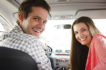 Happy young couple sitting in car, USA, New Jersey, Jersey City