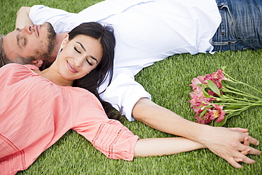 Couple lying together on grass, USA, New Jersey, Jersey City
