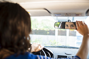 Woman adjusting rear view mirror in car