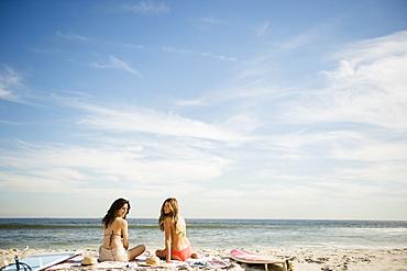 Two women relaxing on beach, Rockaway Beach, New York