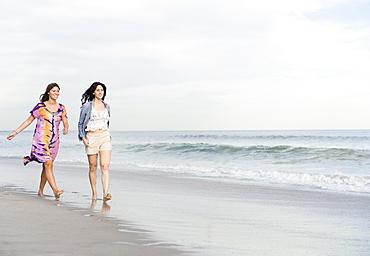 Two women walking on beach, Rockaway Beach, New York