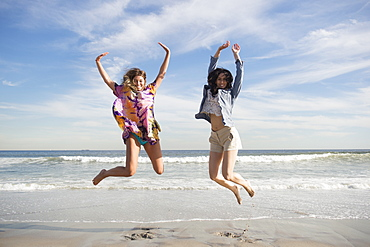 Two young women jumping on beach, Rockaway Beach, New York