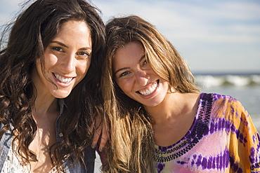 Portrait of two young women on beach, Rockaway Beach, New York
