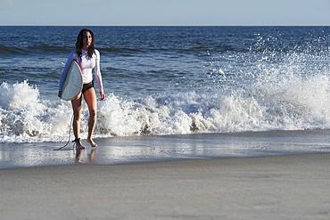 Woman carrying surfboard on beach, Rockaway Beach, New York