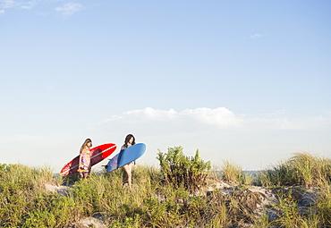 Two female surfers walking on beach, Rockaway Beach, New York