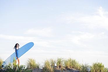 Female surfer walking on beach, Rockaway Beach, New York
