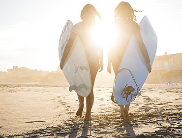 Two female surfers walking on beach at sunset, Rockaway Beach, New York