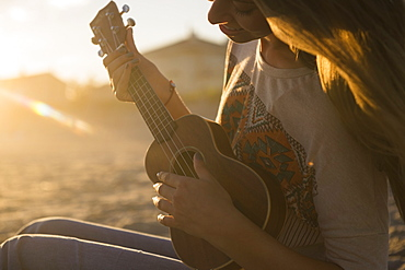 Woman playing ukulele at sunset, Rockaway Beach, New York
