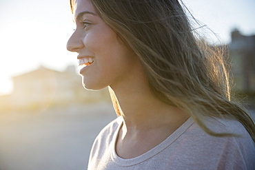 Profile of smiling woman at sunset, Rockaway Beach, New York