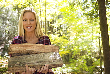 Portrait of woman holding logs in forest, Newtown, Connecticut