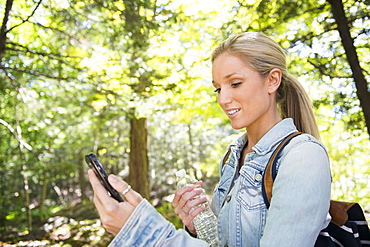Woman using cell phone in forest, Newtown, Connecticut