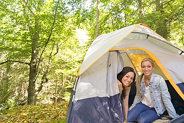 Two women sitting in tent in forest, Newtown, Connecticut