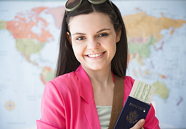 Young woman standing in front of map and holding passport