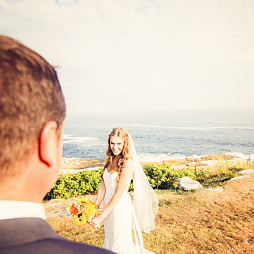 Groom looking at bride, sea in background, USA, Maine, Bristol