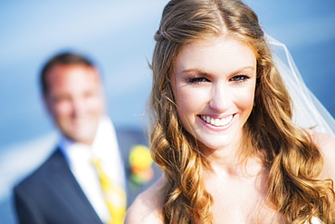 Portrait of smiling bride, groom in background
