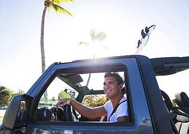 Young man driving car, Jupiter, Florida, USA