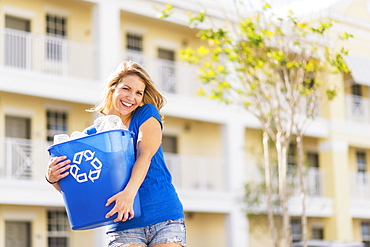 Portrait of woman holding recycling bin, Jupiter, Florida
