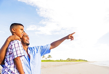 Father and son (10-11) embracing on beach, Jupiter, Florida