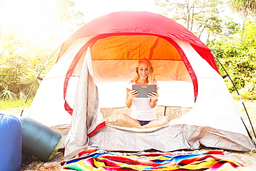 Woman sitting with digital tablet in tent, Tequesta, Florida