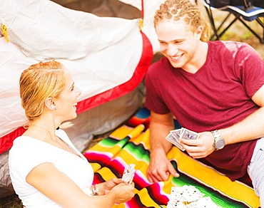 Couple playing cards in front of tent