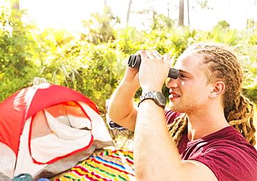 Young man watching birds through binoculars, Tequesta, Florida