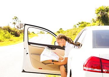 Young man checking map, Tequesta, Florida