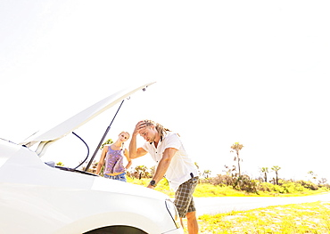 Couple checking car engine, Tequesta, Florida