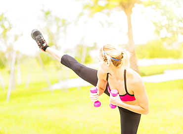 Young woman exercising in park using dumbbells, Jupiter, Florida