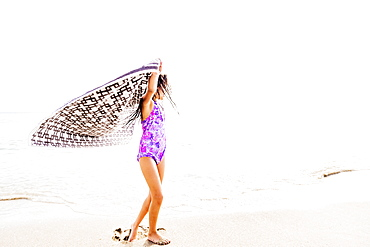 Girl (6-7) spinning on beach, Jupiter, Florida