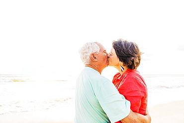 Older couple kissing on beach at sunrise, Jupiter, Florida