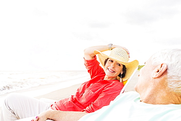 View of couple sitting in lounge chairs on beach, Jupiter, Florida