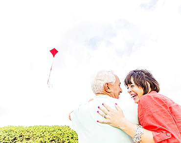 Low-angle view of couple flying kite together