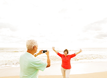 Couple taking pictures on beach at sunrise, Jupiter, Florida