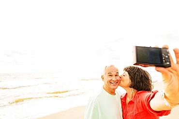 Couple taking selfie on beach at sunrise, Jupiter, Florida