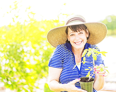 Portrait of smiling woman holding potted plant in garden