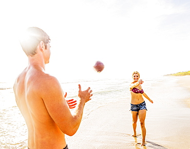 Young couple throwing football on beach, Jupiter, Florida