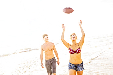 Young woman catching football on beach, Jupiter, Florida