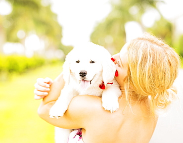 Close-up shot of young woman embracing white puppy, Jupiter, Florida