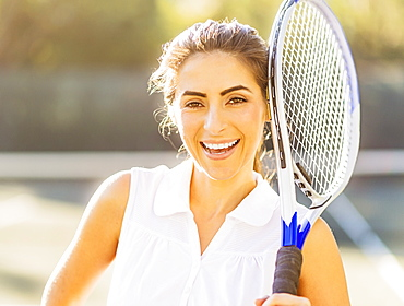 Portrait of smiling young woman holding tennis racket